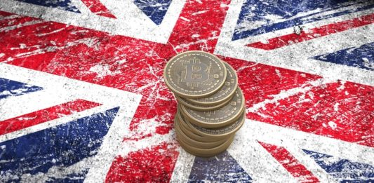 A pile of Bitcoin coins stands on the flag of Britain