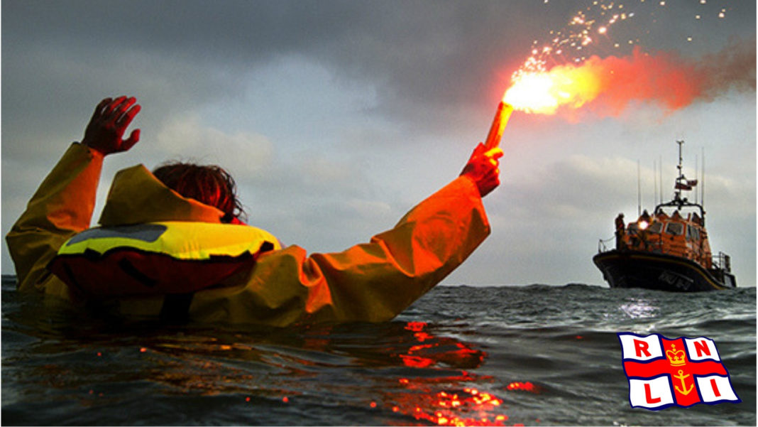 A castaway holding a signal rocket and an RNLI rescue ship in the distance.